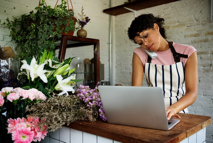 Woman using a laptop while on the phone in a flower shop
