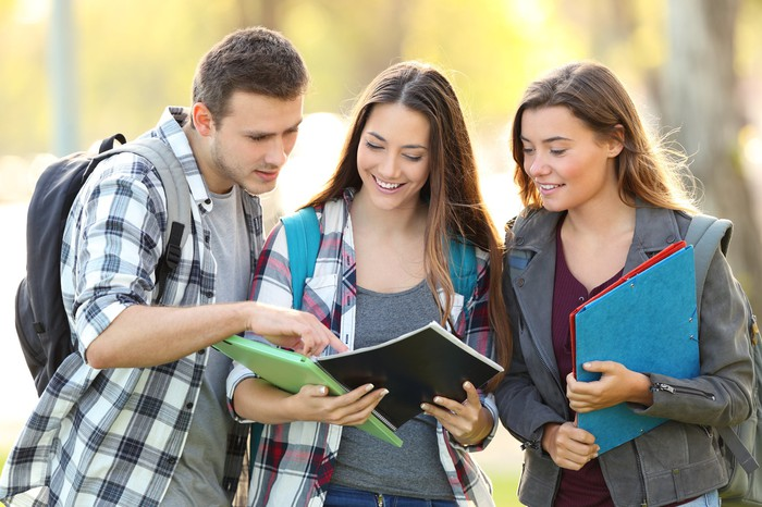 Three college kids with backpacks gather to discuss a textbook in the park.