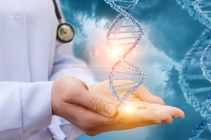 Double helix of DNA floating over the hands of a doctor