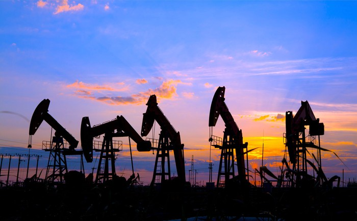 Several oil pumps with the sun setting in the background.