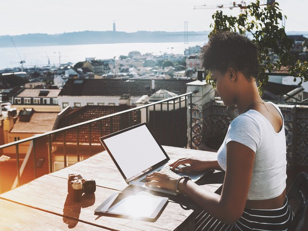 woman typing on laptop on balcony_GettyImages-696108322