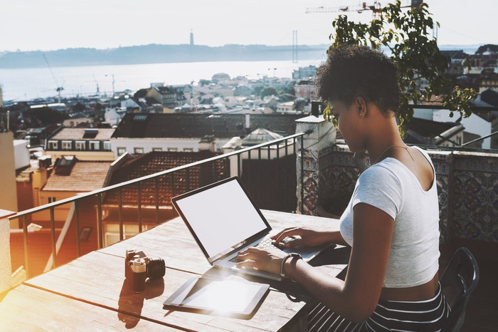Woman typing on a laptop on a balcony that's overlooking water
