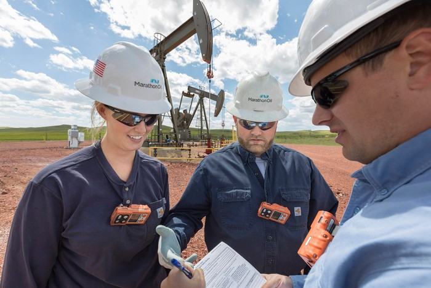 Three workers wearing Marathon hardhats in front of oil wells.