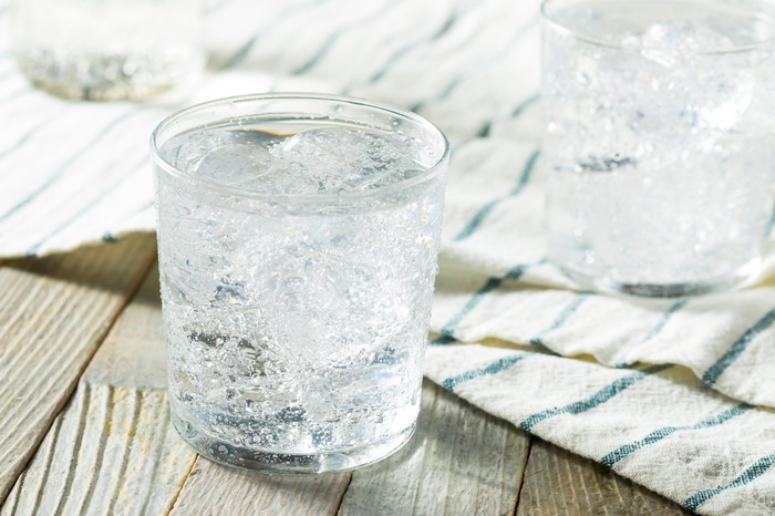 Sparkling water in a glass on a wood table.
