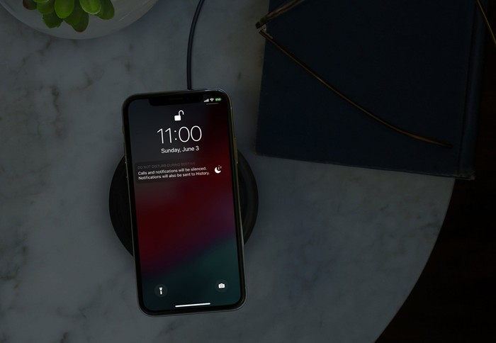 An Apple iPhone X on a wireless charging pad.