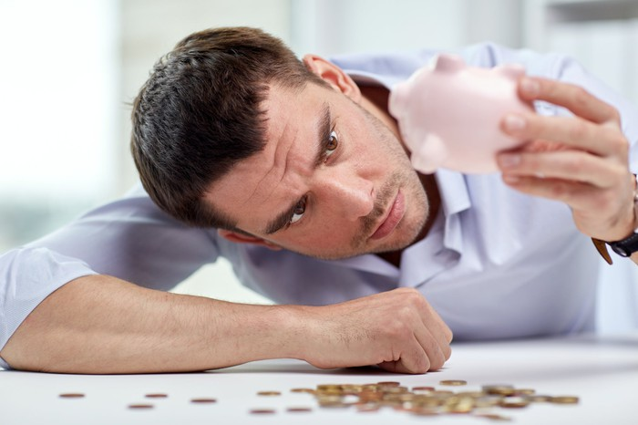 A man turning a small piggy bank upside down and shaking out its coin contents.