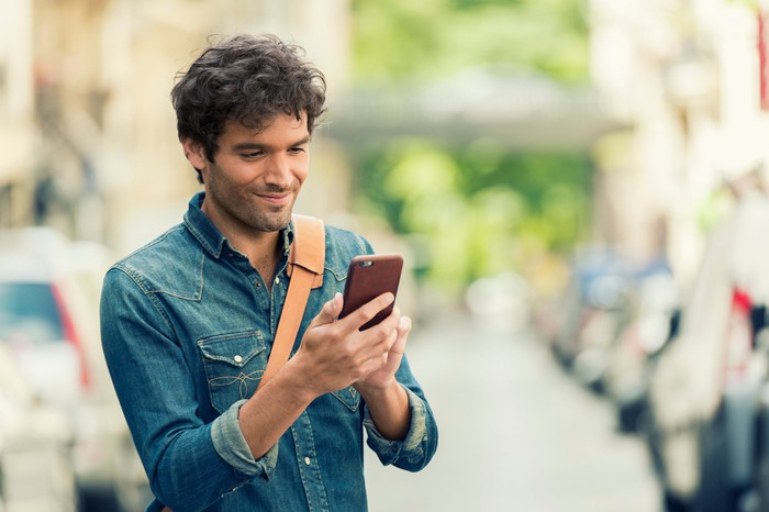 A young man checks his smartphone.