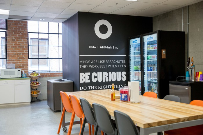 "A breakroom with the Okta logo and various inspiring messages like ""Be Curious"" and ""Do the right thing."""