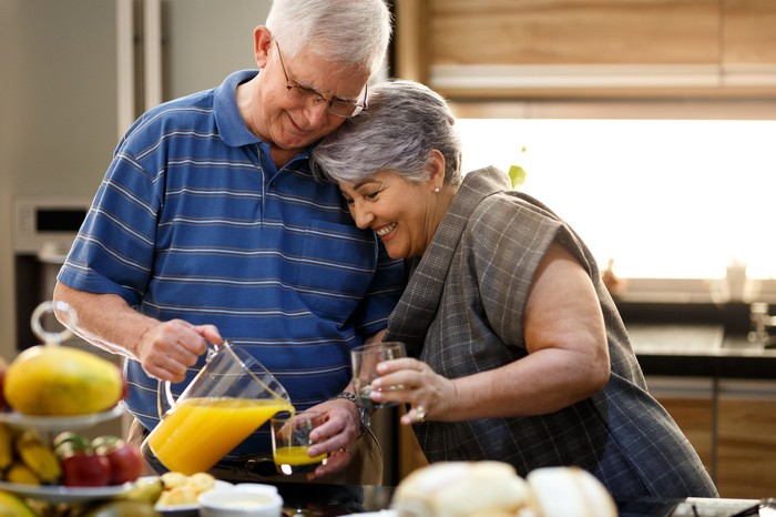 Couple in their 70s pouring orange juice
