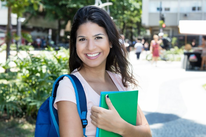 Young female wearing a backpack and holding folders