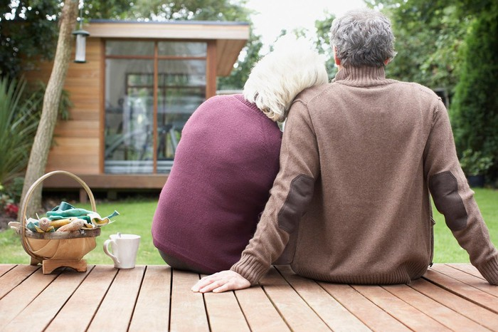 An older couple sit on a deck.