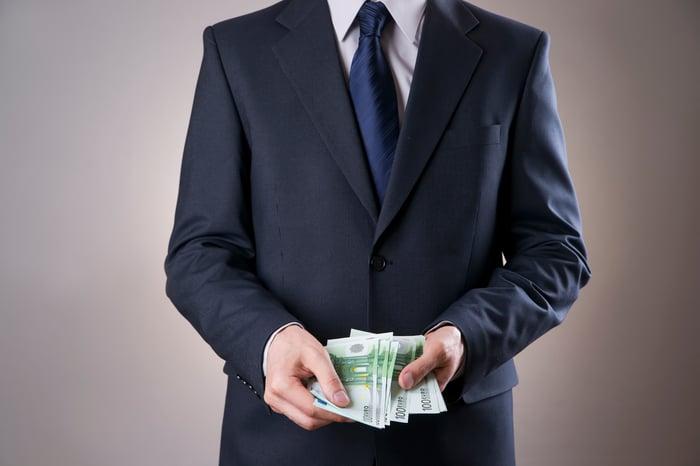 businessman holding wad of bills