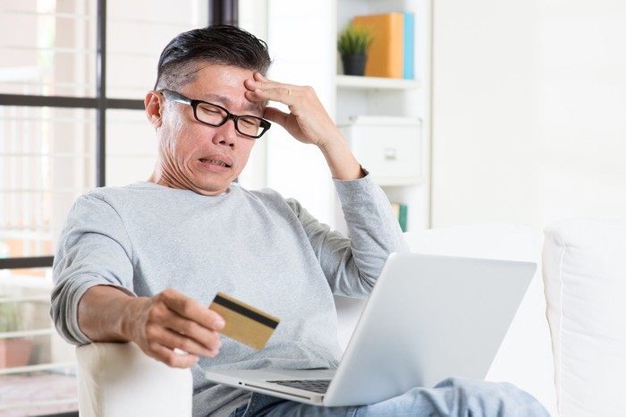A worried man holding a credit card in his right hand while reading material on his laptop.
