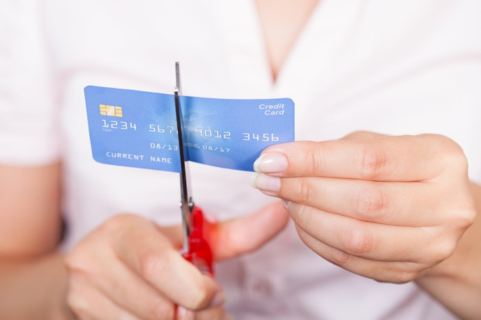 A person cutting a credit card in half with scissors.