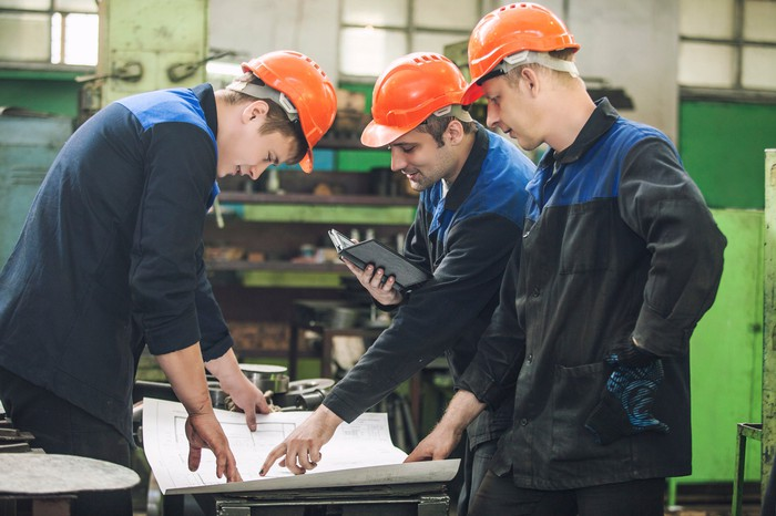 Three men looking over blueprints in an oil processing facility.
