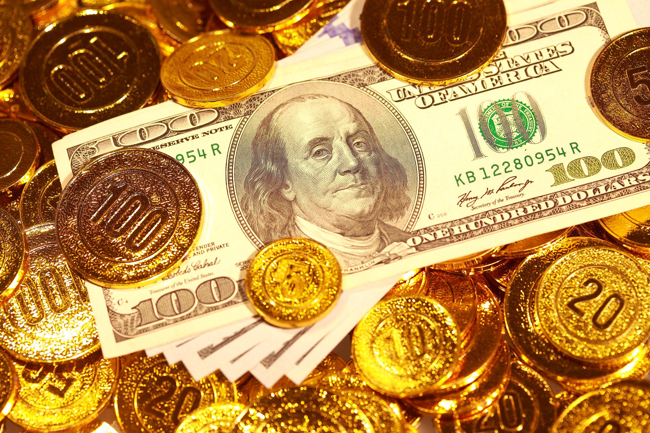 Dollar bills in a golden coin heap.