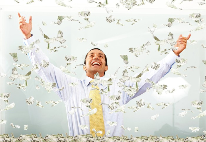 Money falling on a very happy person.