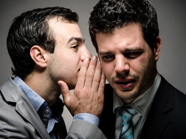 Businessman whispering into the ear of another businessman
