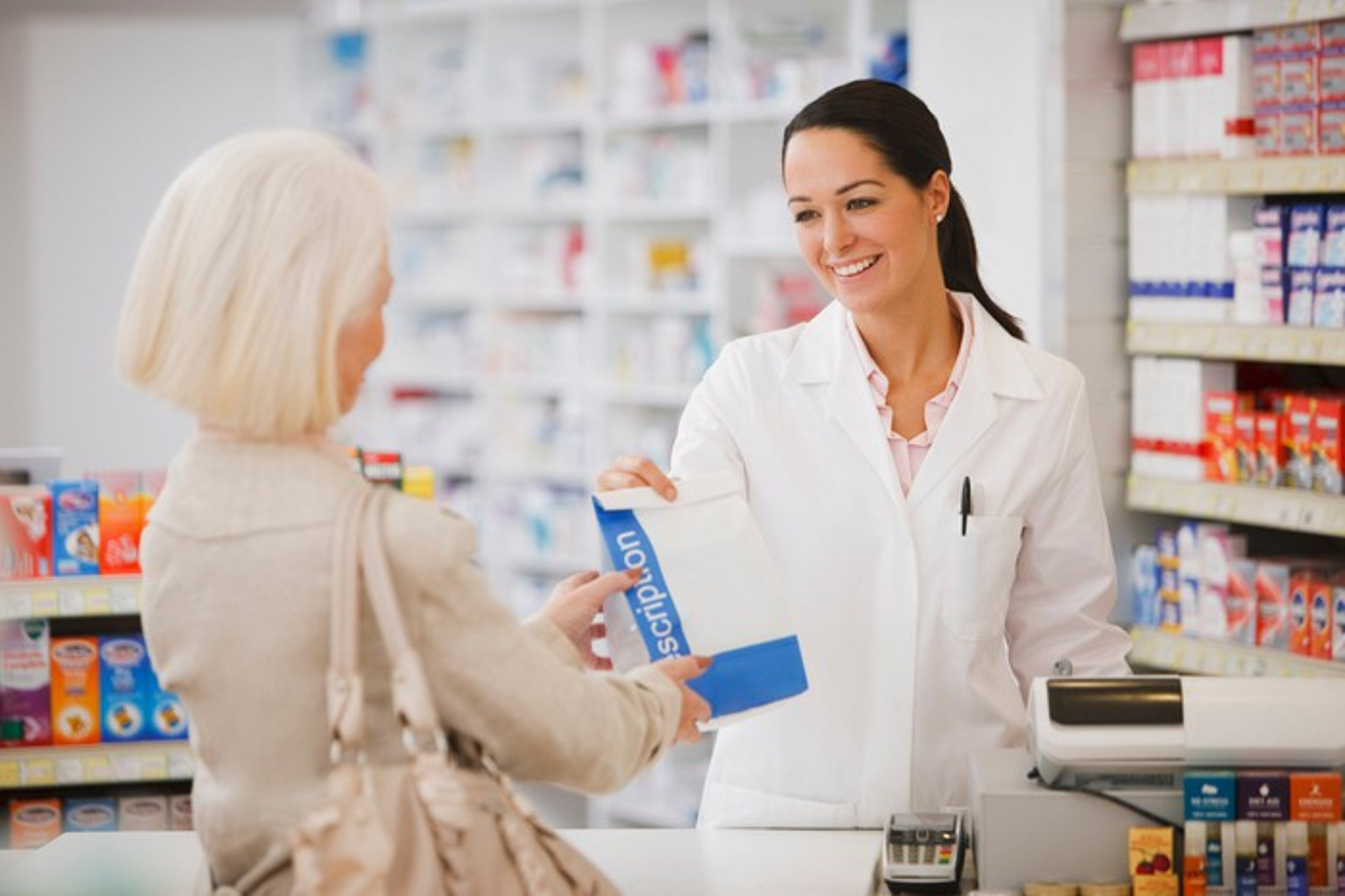 A pharmacist hands out a prescription.