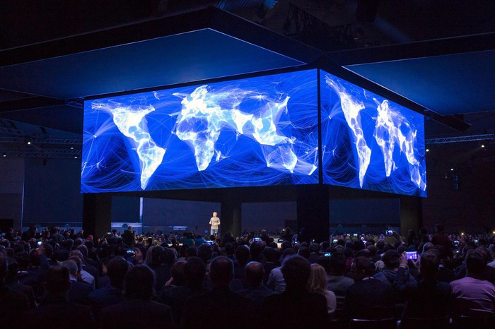 Mark Zuckerberg on stage beneath Facebook's visualization of a connected world