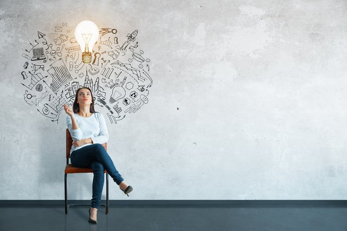A woman in a chair thinking with a light bulb and drawing on the wall behind her.