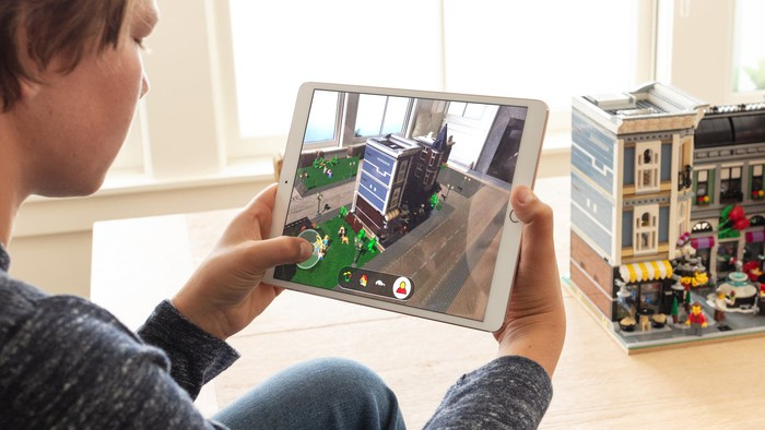 A person looking at a lego set through an iPad, which is applying augmented reality effects.