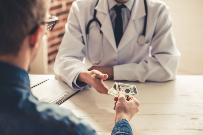Person giving money to a doctor.