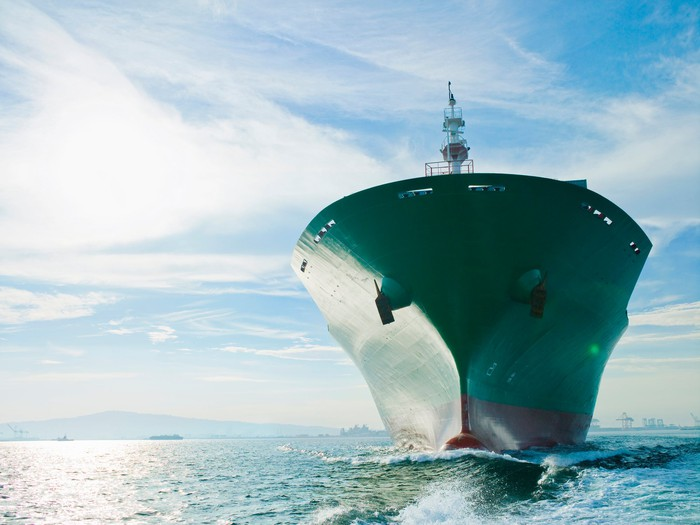 Bow view of cargo ship sailing on ocean.