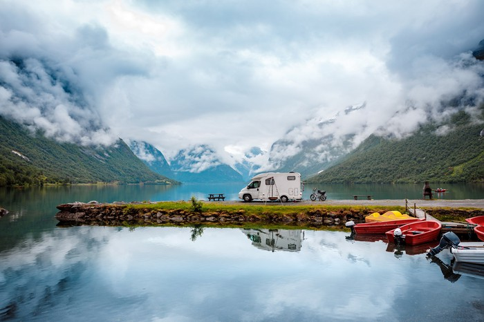 RV parked on a spit of land jutting into a lake, surrounded by boats