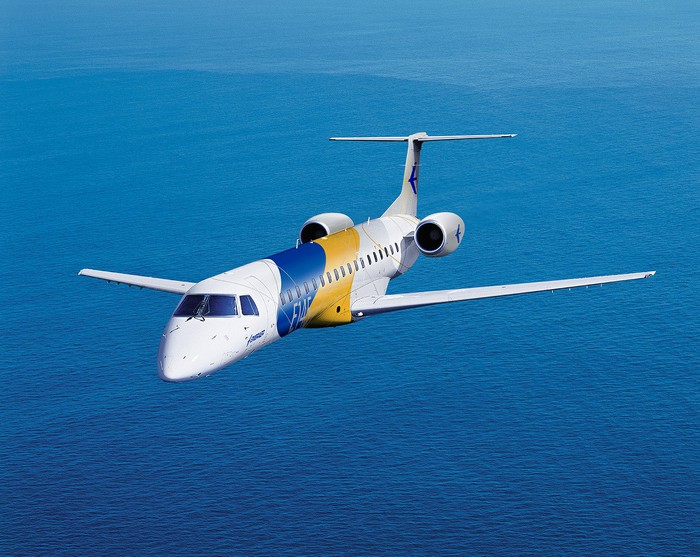 A 50-seat Embraer ERJ-145 flying over water