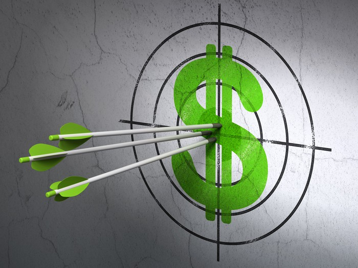 A dollar symbol painted on the wall with a superimposed bull's-eye, with three arrows in the center of the target.