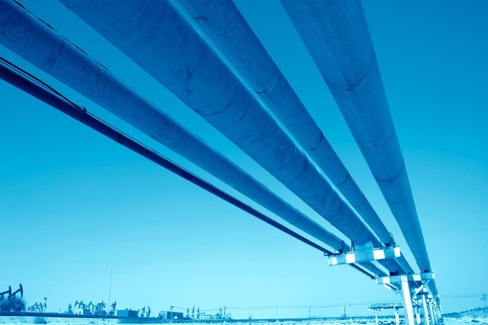 Several oil pipelines overhead with a blue background and oil pumps in the background.