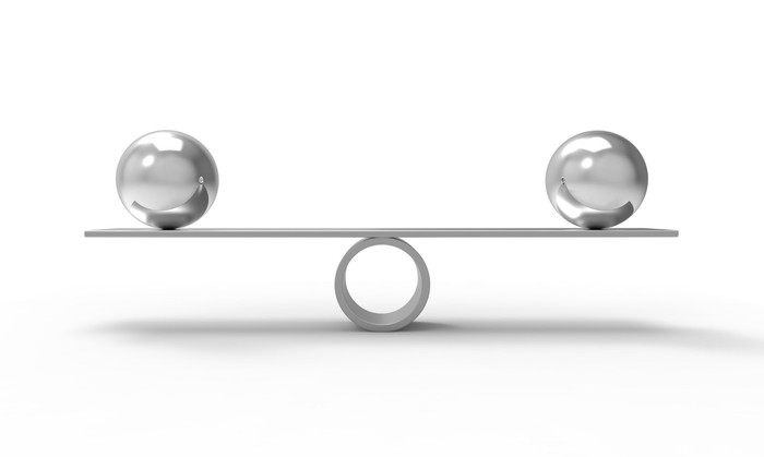 A bar on top of a tube. Balanced on the bar are two spheres, one at each end.