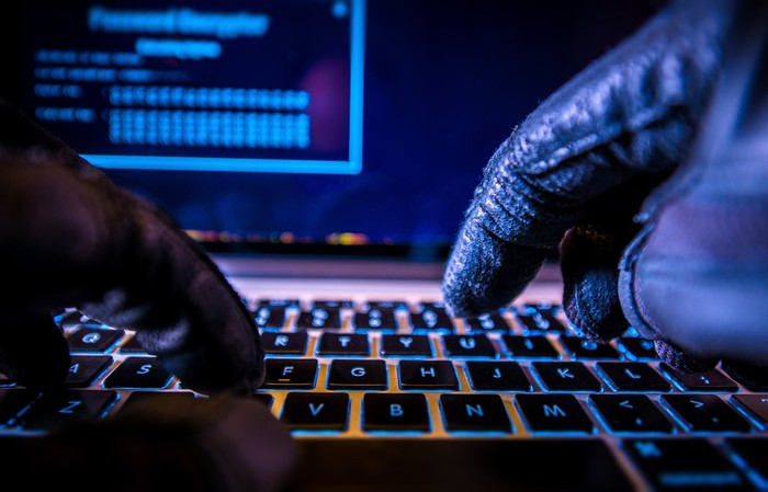 A hacker with black gloves typing on a keyboard in a room with a dark background.