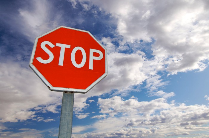 A stop sign with a partly cloudy sky in the background.