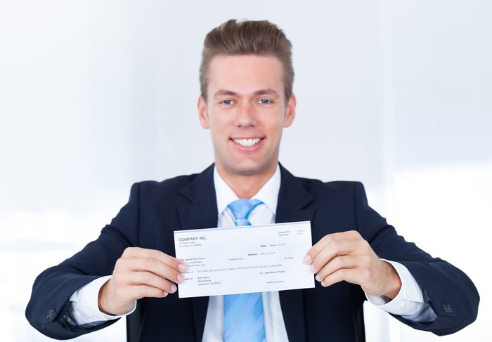 Man in a suit holding a check.