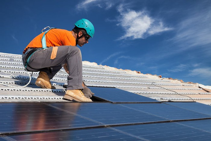 A worker installing a solar panel on a rooftop.