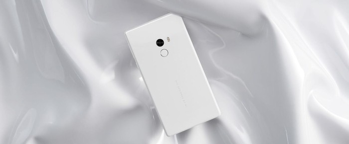 A white Xiaomi phone against a white satin background