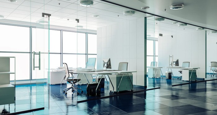 Modern office interior showing glassed-in conference rooms and contemporary furniture.