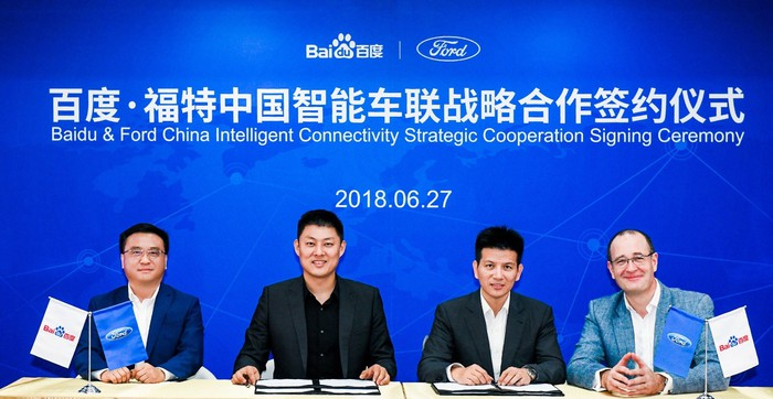 The four executives are seated at a table in front of a blue banner with the Baidu and Ford logos.