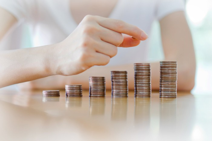 A woman stacking coins up in piles of increasing height.