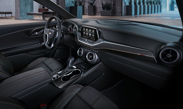 A view of the front seat and dash of a 2019 Chevrolet Blazer, featuring dark leather and fabric with brushed-metal accents.