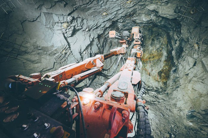 An underground mining vehicle facing a rock wall.