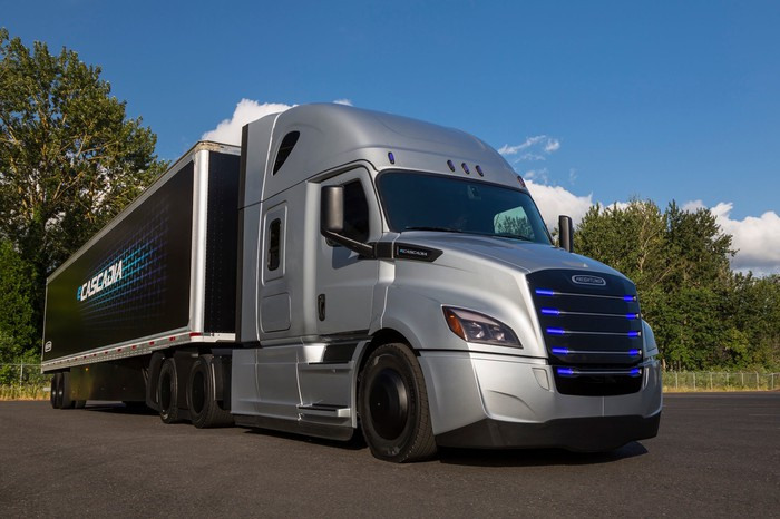 The Freightliner eCascadia, a sleek silver tractor-trailer with blue lights in its grille.