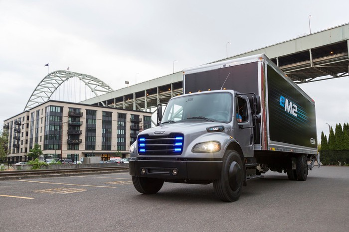 The Freightliner eM2 106, a battery-electric box truck with blue lights in its grille.
