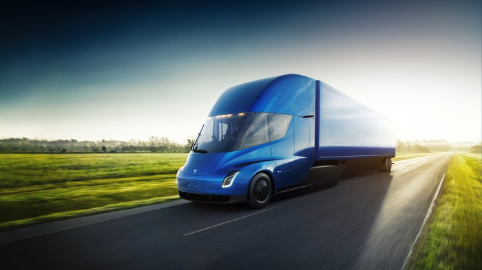A Tesla Semi, a blue tractor-trailer truck, on a rural road.