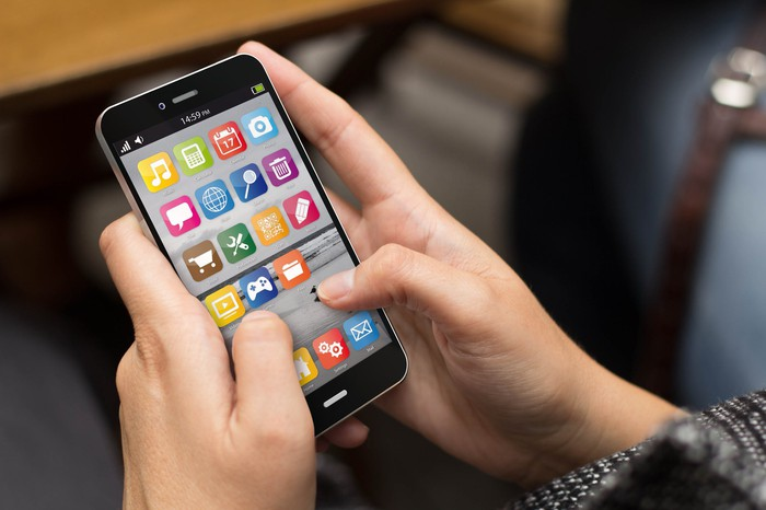 two hands holding a smartphone with many colorful app icons shown on it