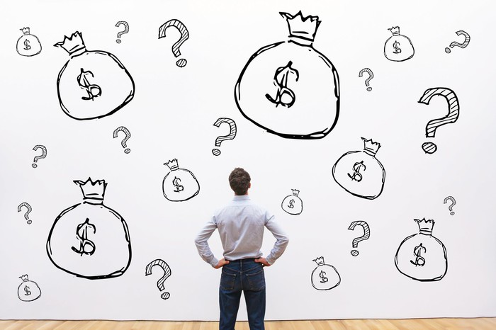 Man with hands on hips looking at wall covered with drawings of money bags and question marks.
