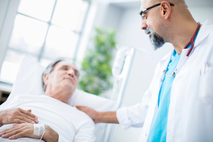 Doctor putting his hand on and elderly patient