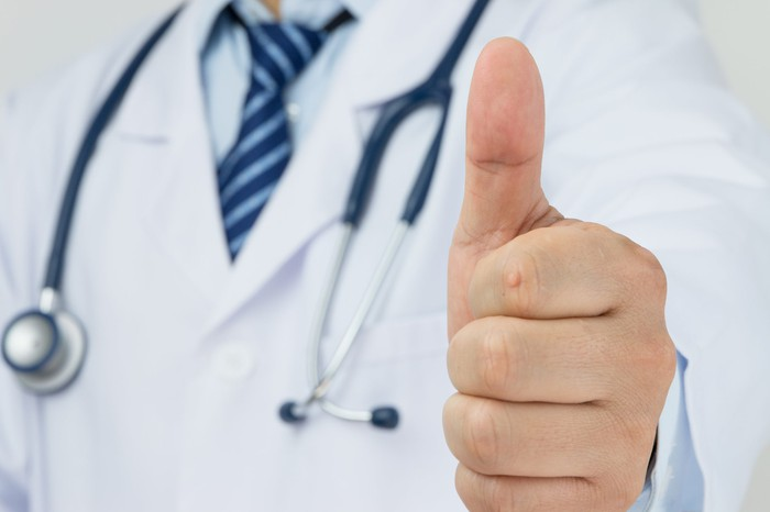 A doctor with a stethoscope around his neck giving the thumbs-up sign.